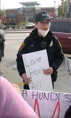 Sheboygan Police officer Dana Fischer holds a sign that says Love Heals All at 14th and Erie during a protest, Monday, June 1, 2020, against the killing of George Floyd, in Sheboygan, Wis.
