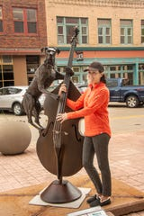 Cyndi Lortan of Dallas, Texas, poses with the Jake on Bass sculpture in downtown Sioux Falls.