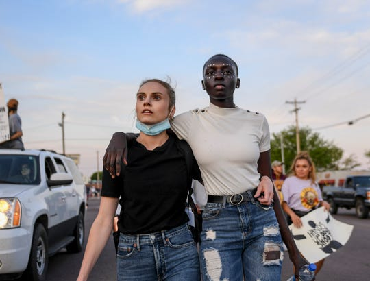 Liz Magnuson and Mariyom Deng march the streets in solidarity for George Floyd, a man who was killed by Minneapolis police, on Sunday, May 31, 2020 in Sioux Falls, S.D.