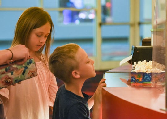 Athena and DJ Christen watch as they receive popcorn before seeing a movie on Friday, June 5, at West Mall 7 theaters in Sioux Falls.