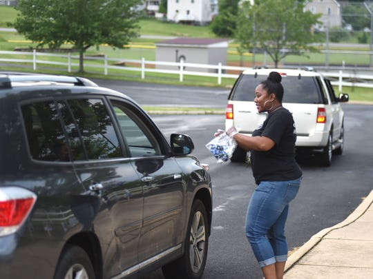 Katrina Lassiter, an assistant principal at Kate Collins Middle School, talks to a student and their family during Thursday's drive-thru celebration for eighth-graders.
