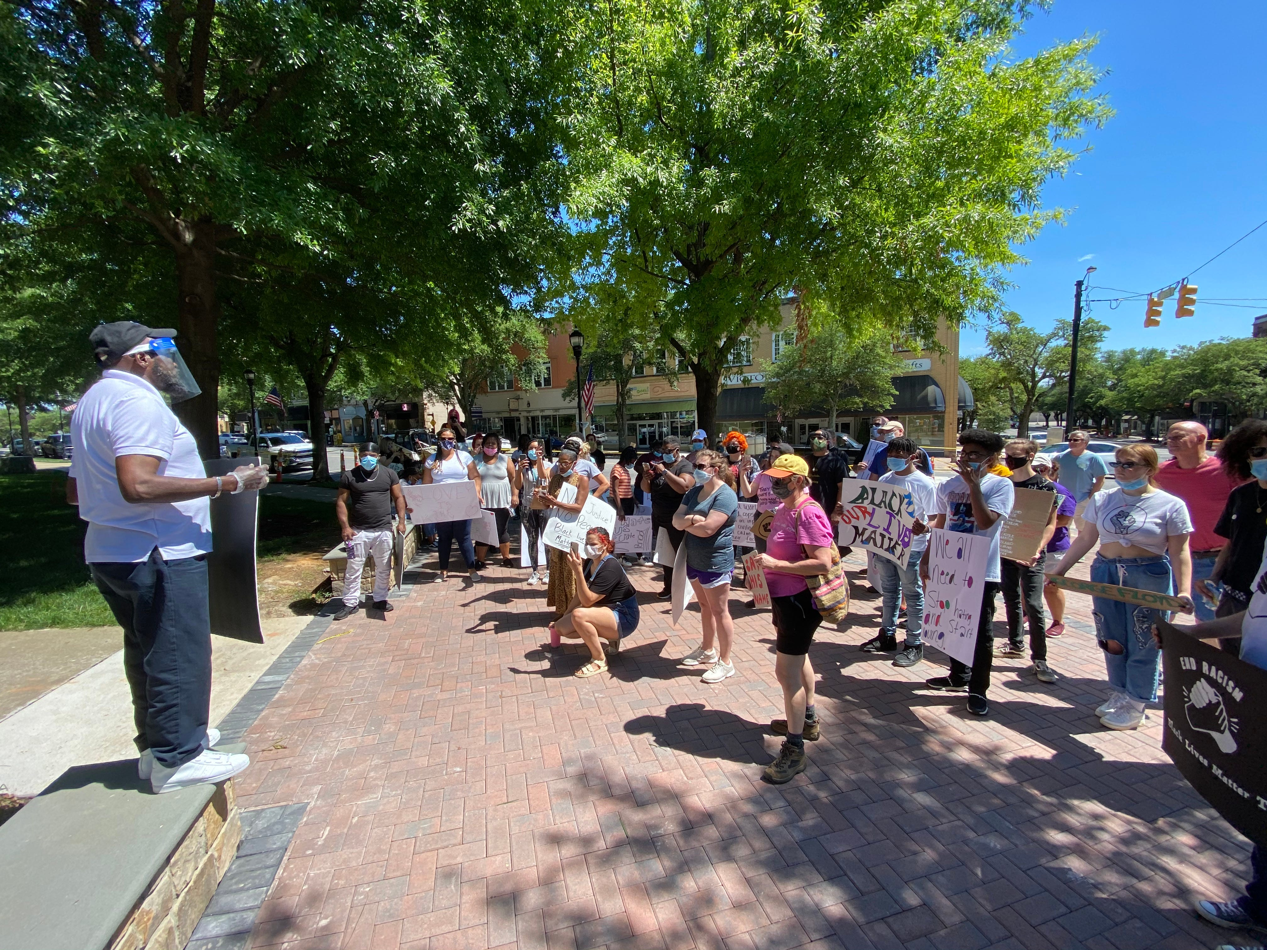 The Rev. Billy Houze speaks to a group of protesters that assembled Sunday.