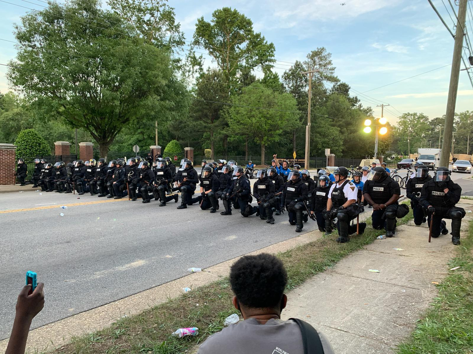 Fayetteville police officers in riot gear take a knee during a protest in Fayetteville on Monday.