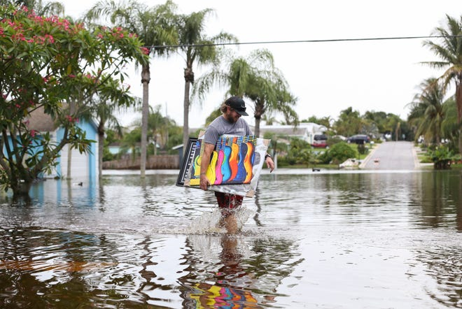 """Colby Besaw, of Hobe Sound, carries personal belongings  while salvaging items from his home that had 3 to 4 inches of flood water damage on Southeast James Street in the Hobe Heights neighborhood on Friday June 5, 2020, in Hobe Sound. Several homes flooded in the area caused by the heavy rainfall this week. """"I spent the last three years remodeling it and this happens,"""" said Besaw. """"I already gutted the house and now I'm just waiting for the water to recede."""""""