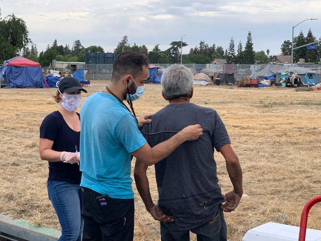 Kaweah Delta Street Medicine team tests people for COVID-19 at a homeless encampment in Tulare on Friday, June 5, 2020.