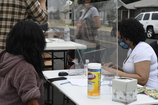 The Tulare County Homeless Outreach Team helps people living in a homeless encampment in Tulare access federal stimulus resources, hygiene kits and housing resources on Friday, June 5, 2020.