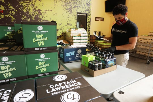 Andres Sanchez builds customer orders for pick-up and delivery at Captain Lawrence Brewery in Elmsford June 3, 2020 which has been offering pick-up and delivery direct to consumers since the pandemic hit and they were forced to close their beer hall.