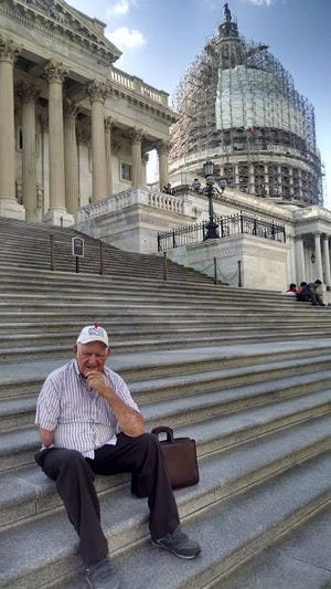 Arden Tewksbury, manager of Pro-Ag sits on the steps of the U.S. Capitol.