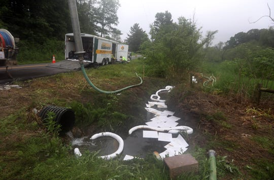 A crew from Zemba Brothers cleans up a gasoline spill on South Pleasant Grove Road Friday morning. The spill resulted from a semi-truck backing into a gas pump at the nearby Marathon Station on US 40.
