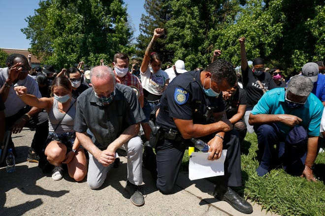 Sacramento Mayor Darrell Steinberg, foreground left, and Sacramento Police Chief Daniel Hahn, foreground right, kneel with others for a moment of silence at a rally in honor of George Floyd, on June 3, 2020, in Sacramento, Calif. Hahn, Steinberg and other local officials, joined hundreds of demonstrators in a peaceful march to a nearby church. Floyd, an African American man, died on May 25 after a white Minneapolis police officer pressed a knee into his neck for several minutes even after he stopped moving and pleading for air.