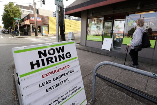 In this photo taken on Thursday, June 4, 2020, a pedestrian wearing a mask passes a reader card announcing a job opening for a Seattle redevelopment company.