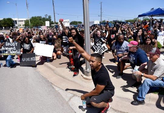 Demonstrators take a knee during a protest march June 6 in memory of George Floyd and other Black Americans who died nationwide in police custody. The peaceful march began at the Abilene Convention Center, proceeded to the Martin Luther King Jr. Bridge and down East Highway 80 to the bridge's sign before returning.