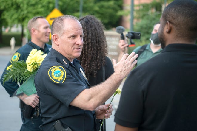Asheville police chief David Zack talks with Kevin Wilkerson outside of the Asheville Police Department about policing in Asheville following a vigil at Pack Square Park on June 5, 2020. The chief says a recent announcement about the APD not responding to some minor crimes in person is an attempt to free up officers to respond to more serious crimes, and to improve response times to those calls.