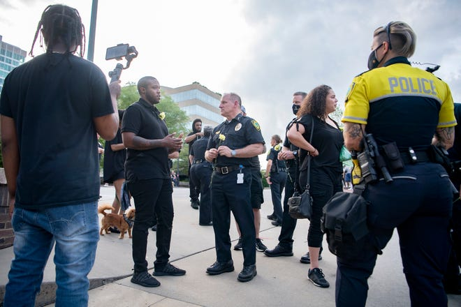 Asheville police chief David Zack, center, talks with Kevin Wilkerson outside of the Asheville Police Department about policing in Asheville following a peaceful vigil at Pack Square Park on June 5, 2020. The vigil honored, among others, George Floyd who was killed by Minneapolis police and Breonna Taylor who was killed by Louisville police and would have been celebrating her 27th birthday.