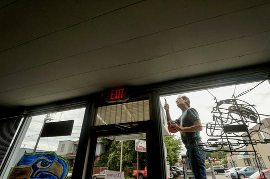 Longtime customer and retired welder Bob Ross is framed in the front window as he paints the facade of Monica's Social Club in Bremerton on Friday. Monica's is one of the Kitsap restaurants in which the owners took the downtime to make improvements to their business as they waited for reopening.