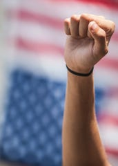 A protestor puts his fist in the air during a Black Lives Matter protest on Saturday, June 6, 2020, in front of the Ross County Courthouse. The gesture has long been a symbol of black liberation. An upside-down American flag hangs in the background- a symbol of dire distress and extreme danger to life or property.