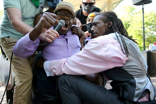 Robert Harris is lifted out of his wheelchair to take a knee as demonstrators protest the death of George Floyd at a Neighborhoods United event June 6, 2020, in Cincinnati.