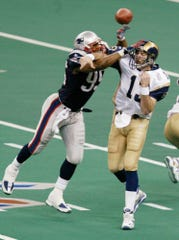 New England Patriots linebacker Roman Phifer gets to St. Louis Rams quarterback Kurt Warner during the second half of Super Bowl XXXVI at the Superdome on Feb. 2, 2002, in New Orleans.