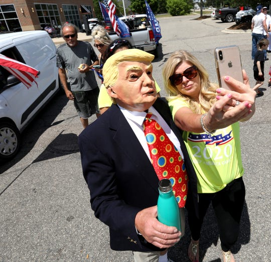 Anne Marie Tomich, 53 of Clinton Township wanted a selfie with Tom Stackpool, 74 of Algonac who was walking around the Trump rally with his mask on to the delight of many people at the event in Shelby Township, Michigan on Saturday, June 6, 2020.