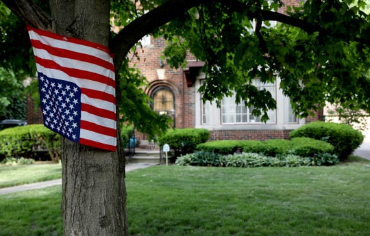 An upside down American flag, known as a sign of dire distress is nailed to a tree at a home in the University District of Detroit on Wednesday, June 3, 2020.
