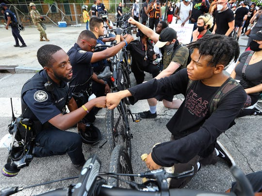 In this June 3, 2020, file photo, Atlanta Police Officer J. Coleman, left, and protester Elijah Raffington, of Sandy Springs, fist bump in a symbolic gesture of solidarity outside the CNN Center at Olympic Park, in Atlanta.