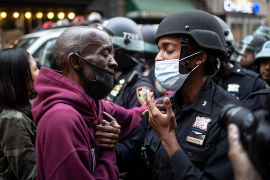 In this June 2, 2020, file photo, a protester and a police officer greet in the middle of a standoff during a solidarity rally calling for justice over the death of George Floyd in New York.