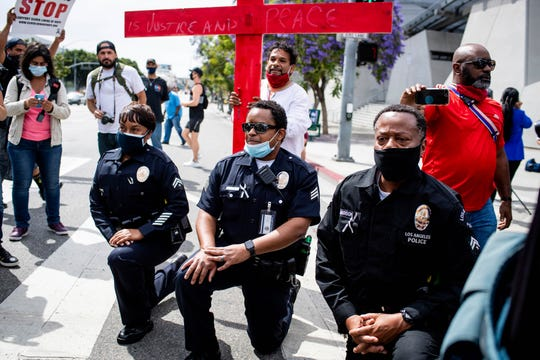 In this June 2, 2020, file photo, Los Angeles police officers take a knee with clergy and marchers at LAPD Headquarters during a demonstration demanding justice for George Floyd in Los Angeles.