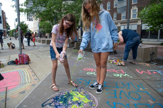 Sisters Claire Knight, 8, left, and Addie Marksberry, 11, use a corn starch artistic medium at the children's protest rally at Ford Center in Evansville Saturday afternoon, June 6, 2020. All of the chalk was sold out when they went shopping, so they were forced to make their own.