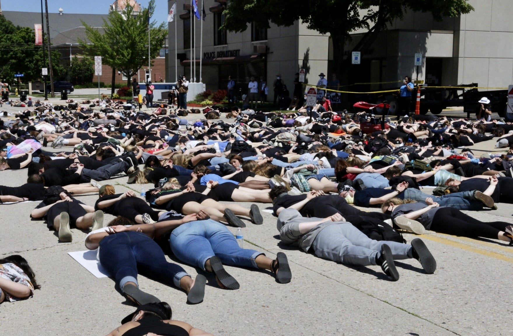 People lay on the concrete for 8 minutes and 40 seconds during in front of the Green Bay Police headquarters during the March for Black lives, Saturday, June 6, 2020, in Green Bay, Wis.