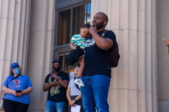 Damion Proctor addressed the crowd while holding his young son Logan while sharing his thoughts and concerns about the world his son will experience as he grows up.