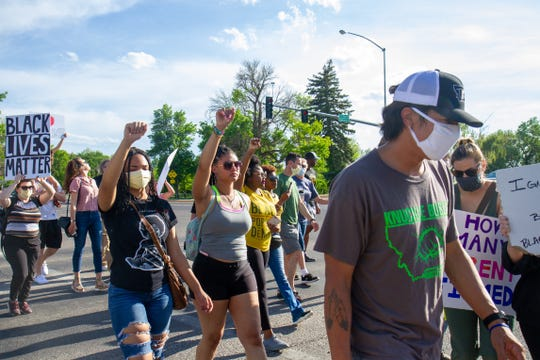 Faith Ariegwe (left) and her sister Kierra Haggerty cross the crosswalk with their fists raised as they make their way to the Federal Courthouse during the National Day of Action for Black Lives Matter protest in Great Falls on Friday, June 5, 2020.