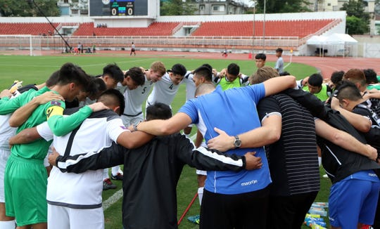 The Guam U19 Men's National Team huddle before the team's match against Japan in the AFC U19 Championship Qualifiers held last year in Vietnam in this file photo. National Team training came to a halt in mid March due to the COVID-19 virus pandemic. After close to three months, selected teams will begin restricted, non-contact training sessions Monday following new procedures to comply with precautionary government mandates, such as social distancing.