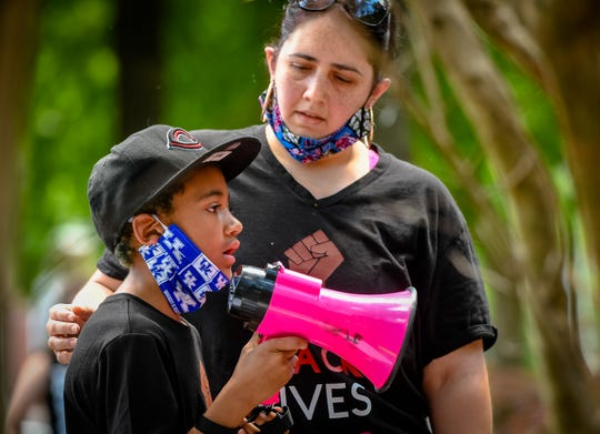 Elizabeth Ahmadi supports nine-year-old, Kayden Mitchell while he summons the courage to speak to protesters gathered for at a Rally Against the Injustice held in Henderson's Central Park Saturday, June 6, 2020.