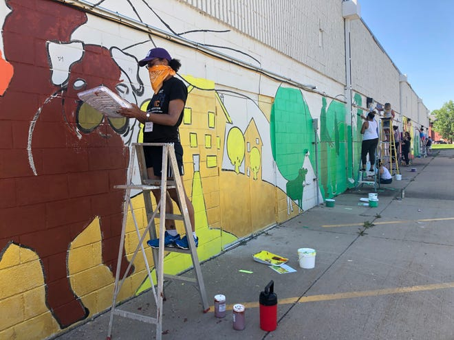Angie Jordan paints a pug on a mural located on Broadway Street behind Faith Academy private school, Friday, June 5, 2020, in Iowa City.