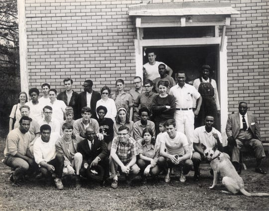 CORE volunteers, workers and local activists gather to rebuild Pleasant Grove Baptist Church in Jonesboro, one of the two black churches destroyed by arsonists in January 1965. The Deacons protected college student volunteers who aided the rebuild project. Shown are, front row, left to right, Alvin Culpepper, unidentified volunteer, Charlie Fenton (CORE), Rev. E. H. Houston (church pastor), Duffy (dog). Second row, fifth from left, Cathy Patterson (CORE). Top row, fourth from left, Ronnie Moore (CORE). In the doorway, left to right, Mike Lesser (CORE) and Jonesboro residents Eddie Scott, Lee Gilbert, and Freeman Knox.