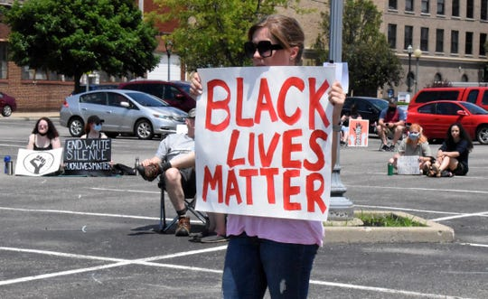 Protesters hold up signs supporting Black Lives Matter and condemning racism at the Fairfield County Job and Family Services parking lot in Lancaster June 6.