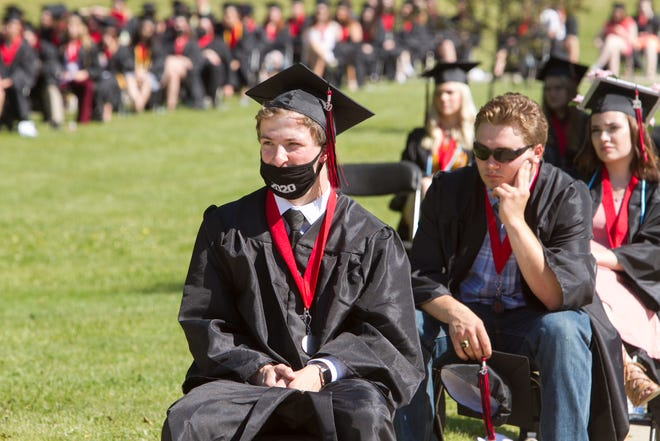 Pinckney 2020 graduating senior Cameron Pollock wears a face mask emblazoned with the year of his commencement at his graduation during the COVID-19 pandemic, Saturday, June 6, 2020.