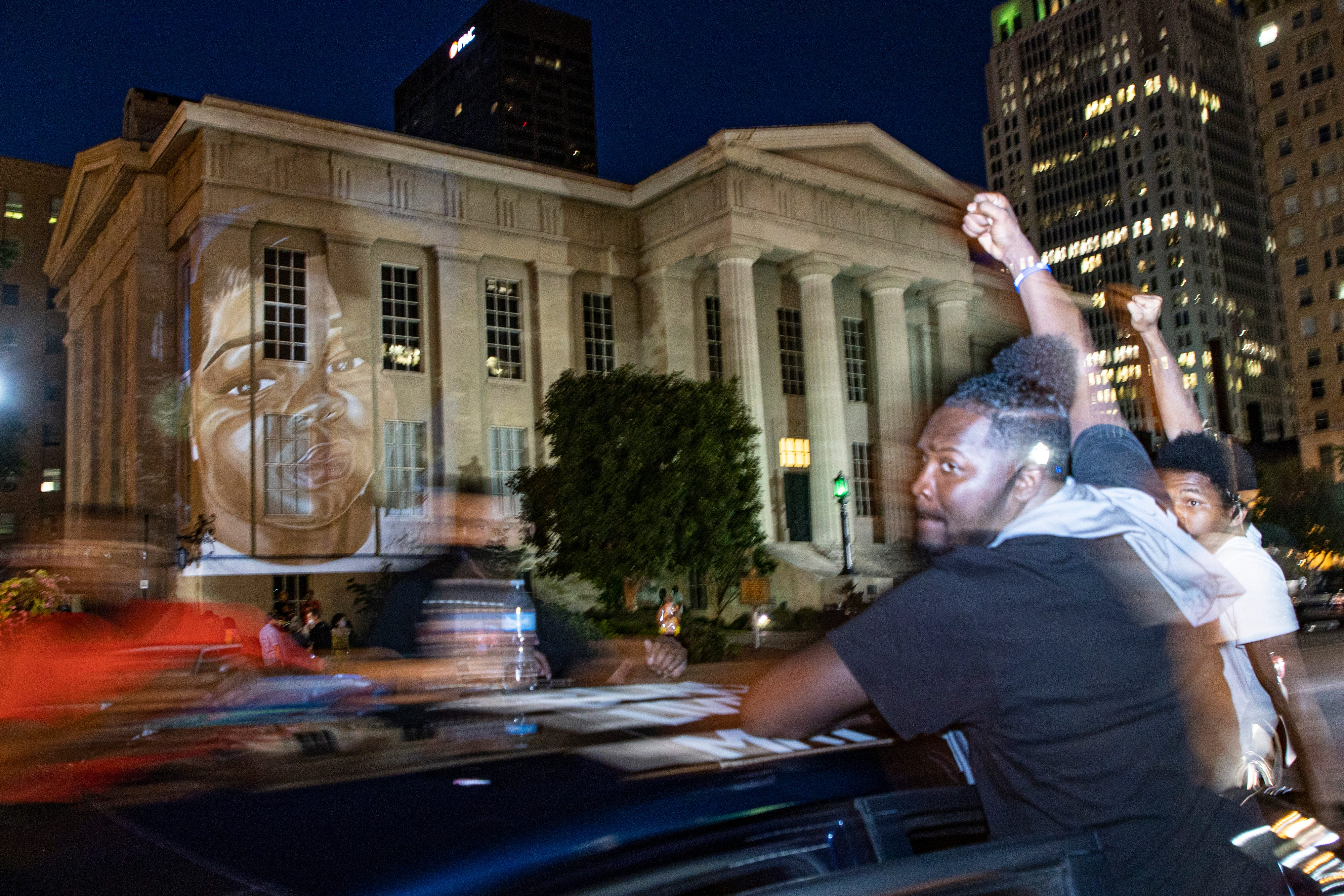 Protesters drive past a portrait of Breonna Taylor, made by local artist Jaylin Stewart, is projected onto Metro Hall during a celebration and protest of police brutality and justice on what would have been the 27th birthday of Breonna Taylor in Louisville. June 5, 2020
