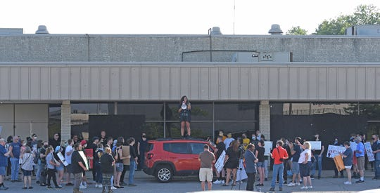 Jordyn Sims speaks to protesters from the roof of a car in the Richland Mall parking lot Friday evening.