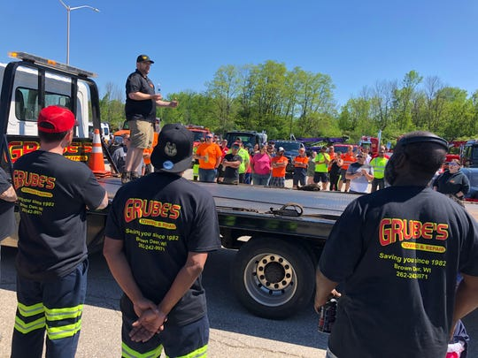 Tim Grube, owner of Grube's Towing and Repair, stands on the back of a flatbed truck and speaks to dozens of people who mourned the loss of Ramon Echeverria. Echeverria died on May 29 after being hit by a truck on I-94.