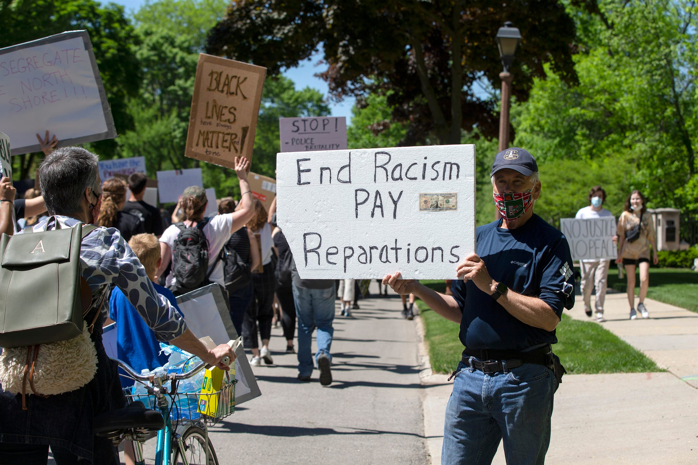 Donald McCauley, resident of Whitefish Bay, shows his sign and support to protesters on Saturday, June 6, 2020.