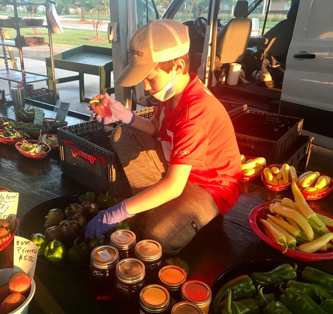 Asher Scully, 9, is the fourth generation of Holleys to work at the Monroe Farmers Market.