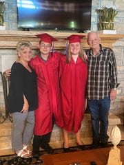 Tammy White (left) and her husband, Ernest White Sr. (right) flank their foster son, Ernest White Jr. and granddaughter Heaven Curtis after they graduated together from Licking Valley High School.