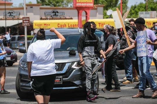 A driver pushes a protester out of the crosswalk at the Lohman Avenue and Walton Boulevard intersection in Las Cruces on Saturday, June 6, 2020.