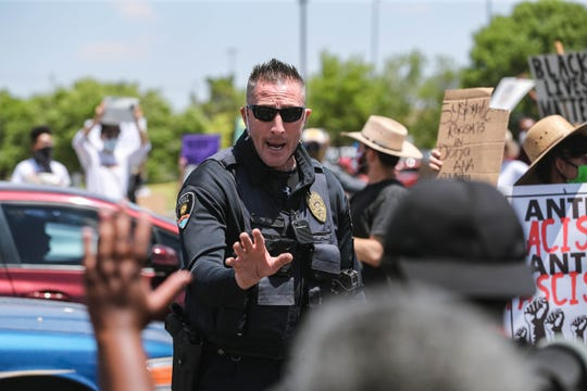 An officer asks demonstrators to let traffic pass as protesters block traffic at the Lohman Avenue and Walton Boulevard intersection in Las Cruces on Saturday, June 6, 2020.