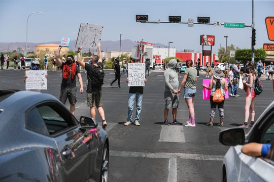 Demonstrators protest police brutality while standing in the crosswalks at the Lohman Avenue and Telshor Boulevard intersection in Las Cruces on Saturday, June 6, 2020.
