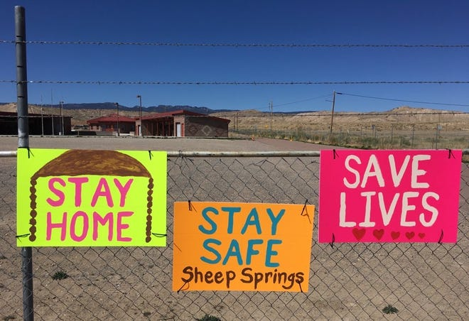 Community members in Sheep Springs are reminded about staying at home to combat the novel coronavirus. The signs are pictured on April 5 at the flea market in Sheep Springs.