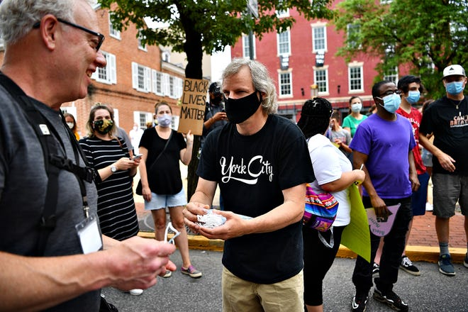 York City Mayor Michael Helfrich offers face masks to those without as about 100 people gather in Continental Square in peaceful protest for George Floyd, to remember those who have died at the hands of police and to celebrate the communication experienced throughout the week between community members and officials in York City, Friday, June 5, 2020. Dawn J. Sagert photo