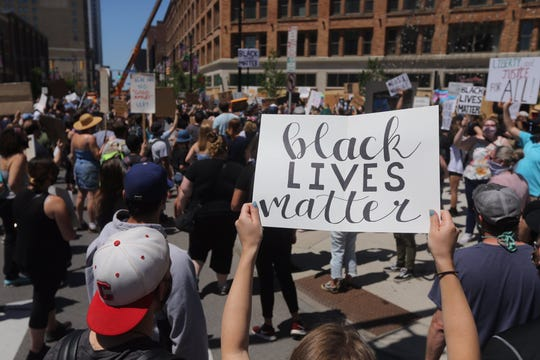 Protesters hold signs at a Black Lives Matter protest in downtown Rochester June 6, 2020.