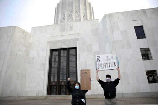 Kari Randel and William Paul McCully hold signs uring a protest of the death of George Floyd in front of the Oregon State Capitol Building in Salem, Oregon, on Friday, June 5, 2020.